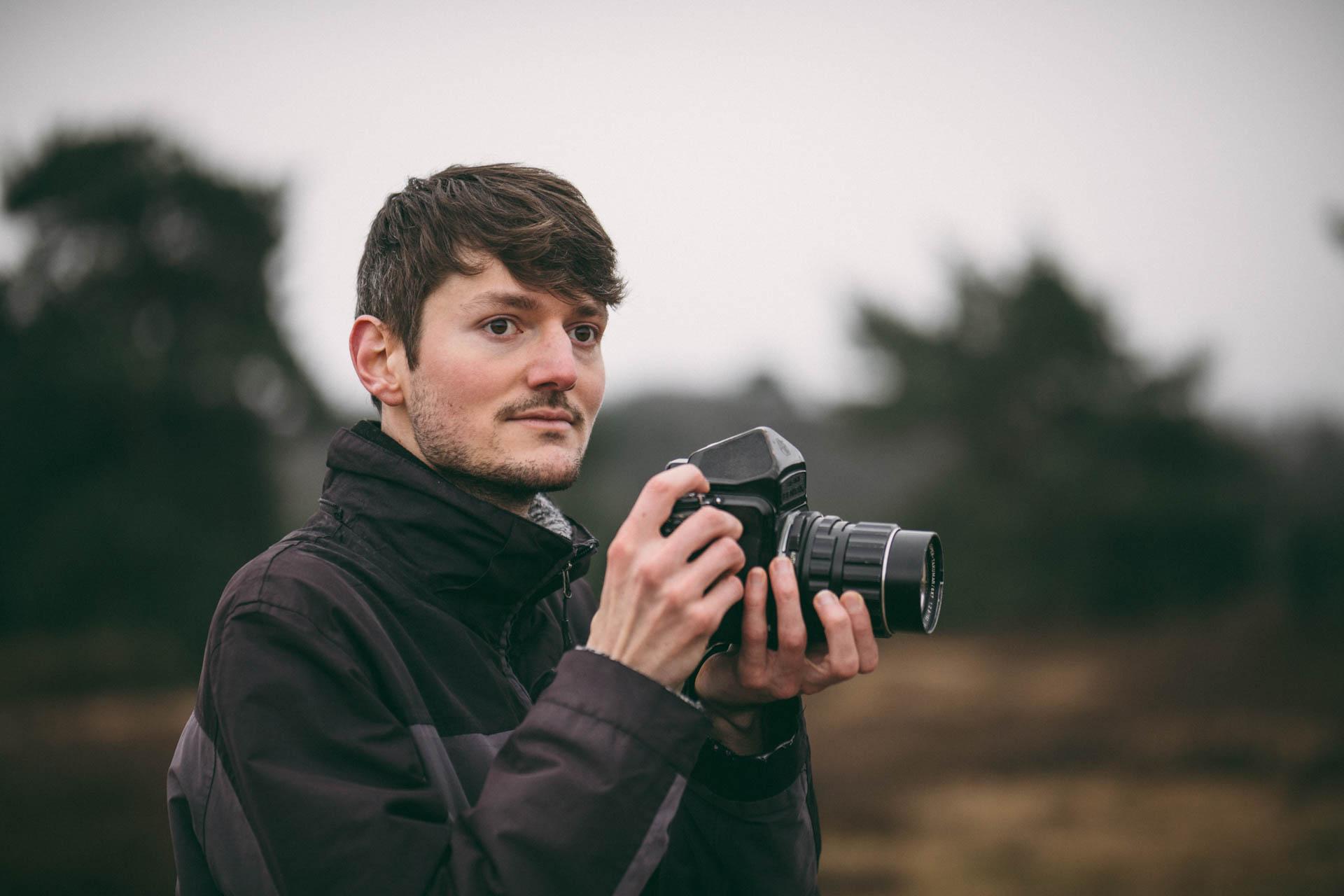 Portrait des Fotografen Benjamin Wohlert mit Kamera in der Hand